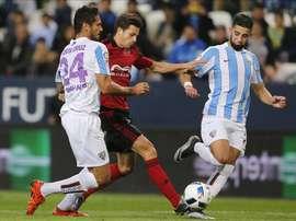 El defensa del Mirandés Ernesto Galán (c) lucha por el balón ante los jugadores del Málaga, el delantero paraguayo Roque Santa Cruz (i) y el centrocampista marroquí Adname Tighadouini, durante el partido de vuelta de los dieciseisavos de la Copa del Rey que se jugó en el estadio de la Rosaleda en Málaga. EFE