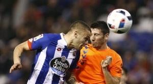 El delantero uruguayo del Deportivo de La Coruña Jonathan Rodríguez (i) disputa un balón con el defensa del Llagostera Aimar (d), durante un partido. EFE/Archivo