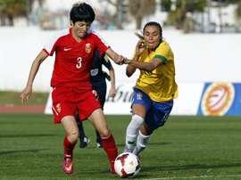 La jugadora de la selección brasileña femenina de fútbol, Marta (d), lucha por el balón con la jugadora de China Wang Shanshan durante un partido. EFE/Archivo