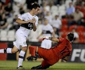Esteban Dreer (d) de Emelec recibe un gol de Cristian Riveros (i) de Olimpia durante el juego del grupo 7 de la Copa Libertadores, en el estadio Defensores Del Chaco e Asunción (Paraguay). EFE