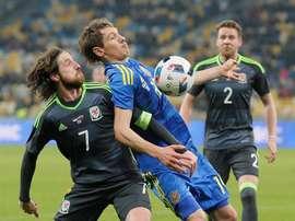 El jugador George Williams (i) de Gales disputa el balón con Denys Harmash (c) de Ucrania. EFE