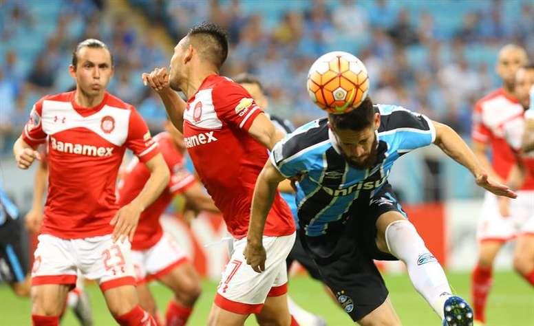 Marcelo Oliveira(d) de Gremio disputa un balón con Mario Quezada (c) de Toluca durante un partido de la Copa Libertadores realizado en el estadio Arena do Gremio en Porto Alegre (Brasil).EFE