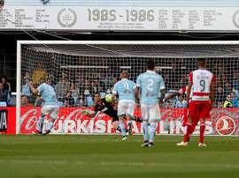El delantero del Celta de Vigo Iago Aspas (i) consigue de penalti el primer gol del equipo gallego frente al portero Andrés Fernández, del Granada CF, durante el partido de Liga de Primera División que se disputa esta noche en el estadio de Balaídos, en Vigo. EFE