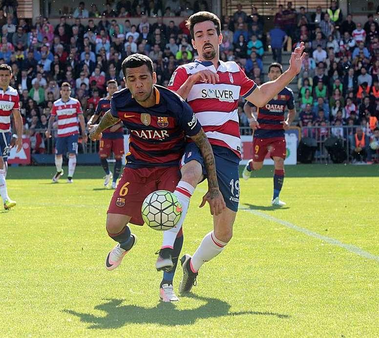 El defensa brasileño del FC Barcelona Dani Alves (i), disputa el balón con el delantero del Granada, Isaac Cuenca (d), durante el partido de la 38 y última jornada de Liga de Primera División jugado en el estadio Nuevo Los Cármenes de Granada, en el que el equipo blaugrana se ha proclamado campeón de la Liga al ganar 0-3 al equipo local. EFE