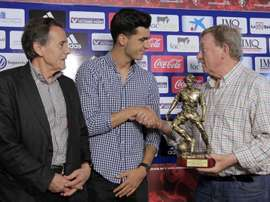 Merino receives a trophy. AFP