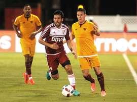 El jugador Kevin Dominique Gameiro (d) de Sevilla FC disputa el balón con Camilo Mayada de River Plate, durante un partido de la