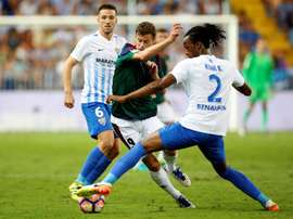 El defensa burkinés del Málaga CF. Koné Bakary (d) lucha el balón con el delantero del Club Atletico Osasuna, Oriol Riera  en el estadio de La Rosaleda, en Málaga. EFE/Archivo