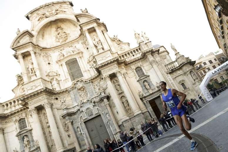 Uno de los participantes pasa ante la catedral de Murcia durante la tradicional carrera de San Silvestre en la ciudad, que ha salido hoy de la Glorieta de España de la capital murciana. EFE