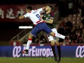 El delantero argentino del Granada Ezequiel Ponce (primer término) golpea al defensa del Osasuna Oier Sanjurjo en el estadio Nuevo Los Cármenes. EFE