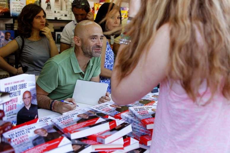 El periodista Antonio Lobato firma ejemplares de libro Volando sobre el asfalto, en la Feria del Libro de Madrid. EFE/Archivo