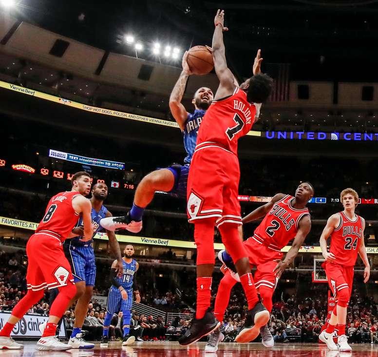 Evan Fournier (i) de Orlando Magic lanza ante Justin Holiday de los Chicago Bulls durante su juego de la NBA en Chicago, Illinois (EE.UU.). EFE