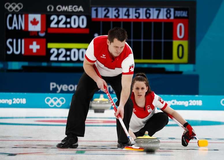 Los suizos Jenny Perret (d) y Martin Riís (i), hoy durante el doble mixto de Curling. EFE