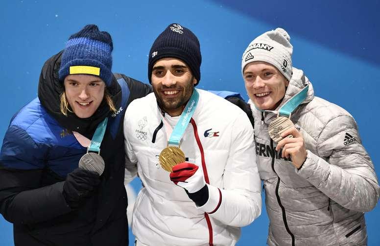 El francés Martin Fourcade (c), el sueco Sebastian Samuelsson (i) y el alemán Benedikt Doll, hoy durante la ceremonia de entrega de medallas de Biatlón. EFE