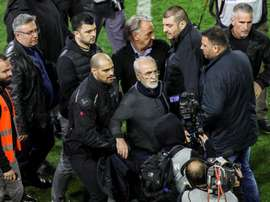 PAOK president Ivan Savvidis (C) is wanted by police after invading the pitch, a gun in his pocket, in Sunday's Super League clash with AEK Athens