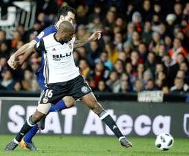 El centrocampista del Barcelona Sergio Busquets (detrás) pelea un balón con el centrocampista francés del Valencia CF Geoffrey Kondogbia, durante un partido. EFE/Archivo
