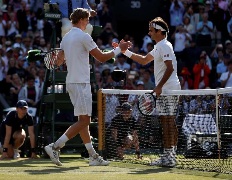 El tenista sudafricano Kevin Anderson (i) estrecha la mano del suizo Roger Federer (d) tras ganar su partido de cuartos de final de Wimbledon disputado en el All England Lawn Tennis Club de Londres, Reino Unido, hoy. EFE