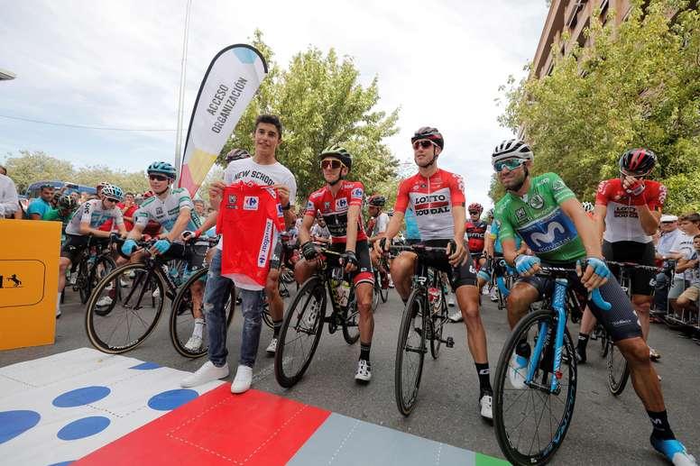 El líder de la clasificación general, Simon Philipe Yates (3d), y el segundo clasificado y maillot verde, Alejandro Valverde (d), posan con el piloto de MotoGP Marc Márquez (4d) al inicio de la decimonovena etapa de la Vuelta Ciclista España 2018 que parte de Lleida y finaliza a Andorra Naturlandia tras 157 kilómetros de recorrido. EFE