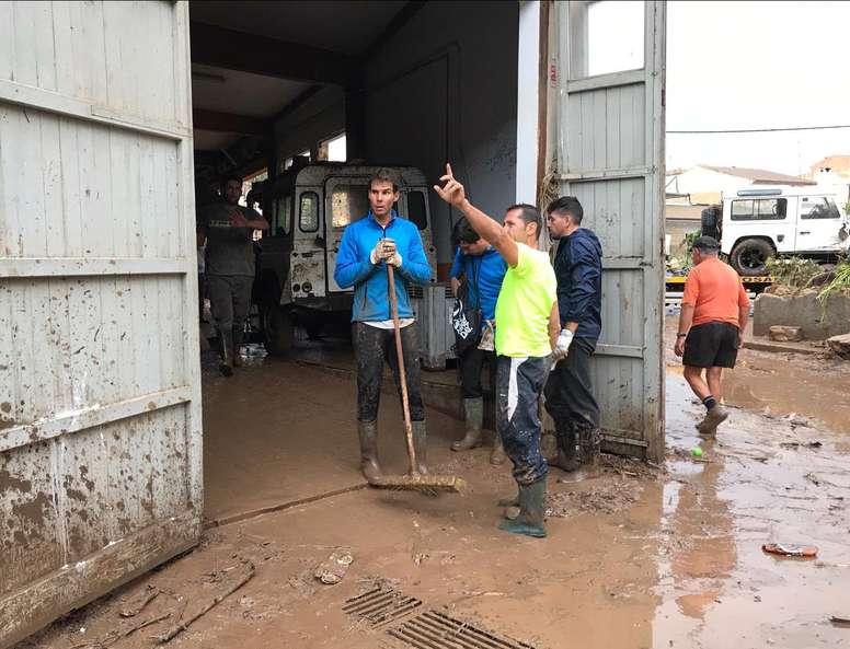 Fotografía facilitada por La Vanguardia, del tenista Rafael Nadal (i), ayudando en las tareas de limpieza en el municipio mallorquín de Sant Llorenç. EFE/La Vanguardia