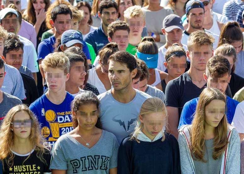 El tenista Rafael Nadal, rodeado de alumnos del Nadal Sports Center, en la localidada mallorquina de Manacor, durante el minuto de silencio en memoria de la víctimas de las inundaciones. EFE