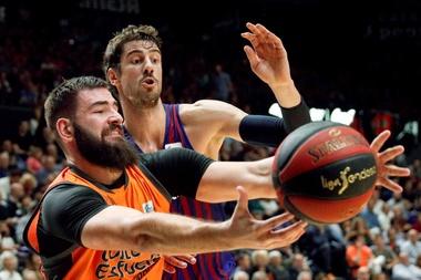 El pivot montenegrino del Valencia Basket, Bojan Dubljevic (i), intenta quedarse el balón ante el jugador croata del Barca Lassa, Ante Tomic, durante el encuentro de la Liga Endesa que disputaron en el pabellón Fuente San Luis, en Valencia. EFE