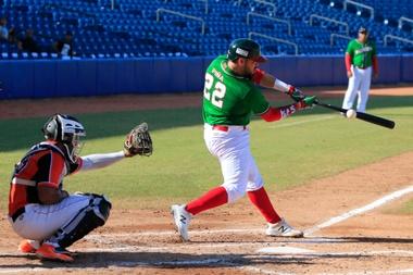 Orlando Piña (d), de la selección mexicana de béisbol, fue registrado al intentar batear una bola, durante un partido contra Holanda por la Copa Mundial de Béisbol Sub-23, en Barranquilla (Colombia). EFE