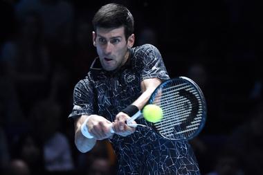 El tenista serbio Novak Djokovic devuelve la pelota al estadounidense John Isner durante la ronda individual masculina en el segundo día del torneo de tenis Finales ATP, en el O2 Arena en Londres (Reino Unido). EFE