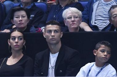 El futbolista portugués Cristiano Ronaldo (c) asiste junto a Georgina Rodríguez (i) y su hijo Cristiano Jr (d) al partido entre el tenista estadounidense John Isner y el serbio Novak Djokovic en el O2 Arena en Londres (Reino Unido). EFE