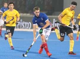 El francés Aristide Coisne (c) intenta zafarse del chino Du Talake (d) durante un partido del Mundial masculino de hockey hierba disputado entre IFrancia y China en el estadio Kalinga de Bhubaneswar (India). EFE
