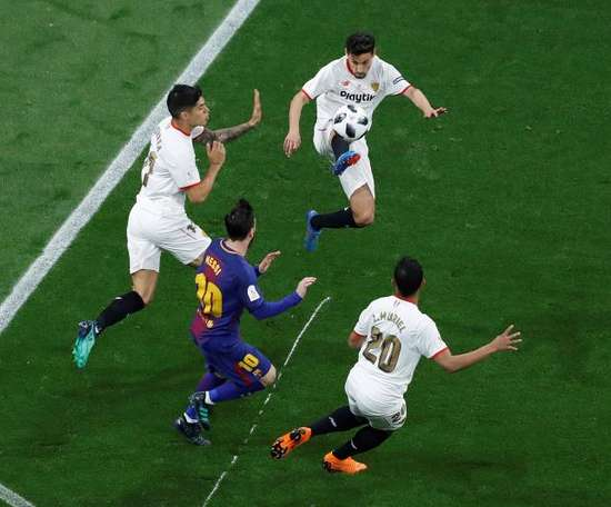 Sevilla players protect the ball from Barcelona forward Lionel Messi. EFE