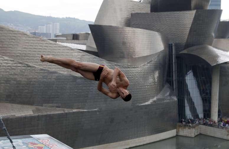 El clavista ucraniano Oleskiy Prygorov en la primera ronda de la competición ante el museo Guggenheim de Bilbao, de saltos de altura de clavadistas más extrema, el Red Bull Cliff Diving, desde el puente de La Salve sobre la ría de Bilbao, el año pasado. EFE/Archivo