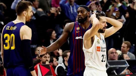 El jugador del Real Madrid Sergio Llull (d) y los del Barcelona Lassa, Víctor Claver (i) y Chris Singleton, durante la final de la Copa del Rey de baloncesto disputada este domingo en el WiZink Center, en Madrid. EFE