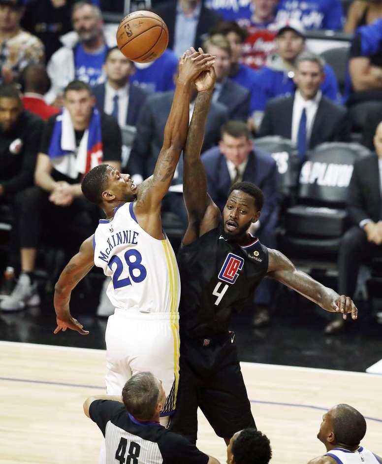 Los aleros de los Golden State Warriors, Alfonzo McKinnie (i) y los Angeles Clippers, Alfonzo McKinnie (d), saltan durante el juego de eliminatorias de la NBA Western Conference Playoffs tres entre Los Angeles Clippers y los Golden State Warriors en el Staples Center de Los Angeles, California, EE. UU.. EFE