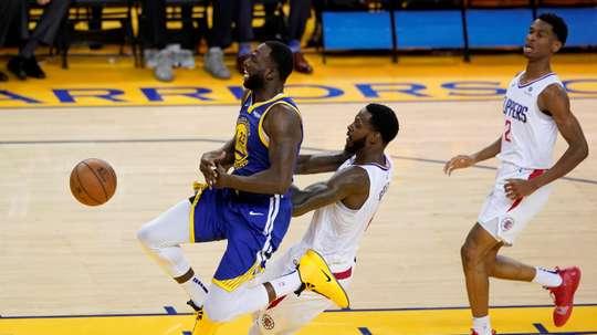 El jugador de los Warriors de Golden State Draymond Green (izq) recibe una falta de JayMychal Green (c), de los Clippers de Los Ángeles, durante el quinto partido de las series clasificatorias de la Conferencia Oeste de la NBA, este miércoles 24, en el pabellón Oracle Arena de Oakland, California (Estados Unidos). EFE