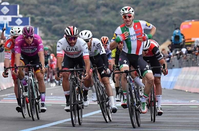El corredor colombiano Fernando Gaviria del equipo UAE Team Emirates (c-i) y el italiano Elia Viviani del equipo Deceuninck-Quick Step (c-d) reaccionan tras cruzar la línea de meta de la tercera etapa del Giro de Italia, de 220 kilómetros, comprendida entre Vinci y Orbetello, este lunes en Italia. EFE