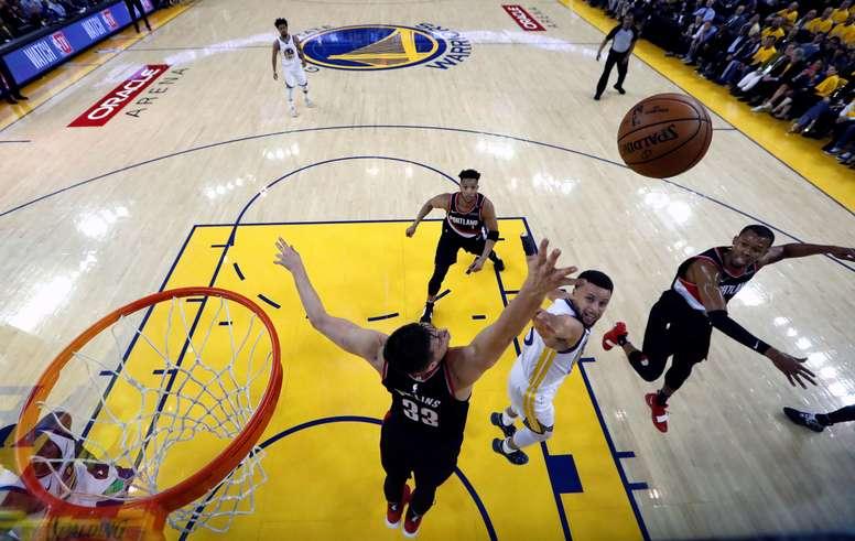 Stephen Curry (c) de los Golden State Warriors en acción contra Zach Collins (i) de Portland Trail Blazers durante su primer juego de las finales de la Conferencia Oeste de la NBA en el Oracle Arena de la ciudad de Oakland, California (EE.UU.). EFE