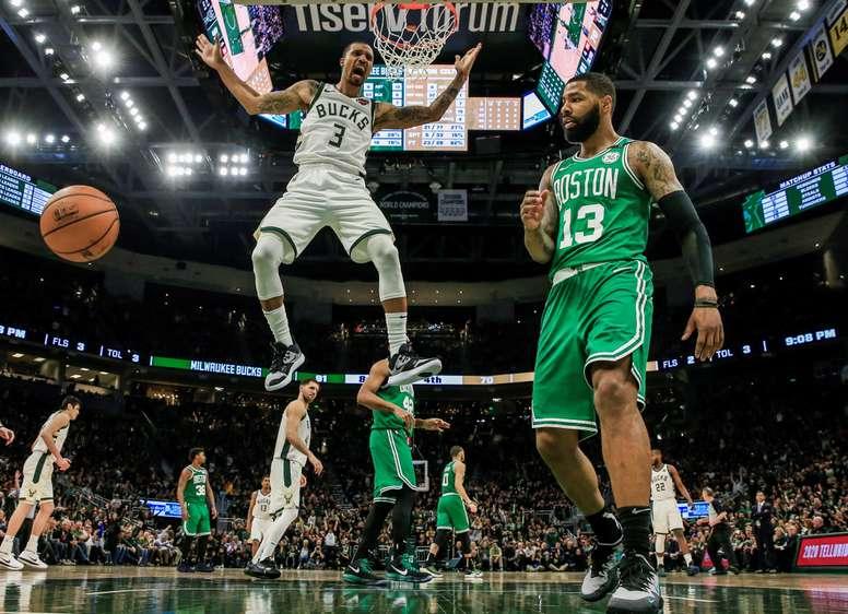 El escolta de los Milwaukee Bucks, George Hill (i), reacciona cuando anota al lado del delantero de los Celtics de Boston Marcus Morris (d) durante un partido. EFE/ Tannen Maury/Archivo