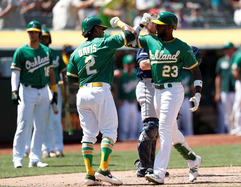 Oakland Athletics Jurickson Profar (R) is greeted at home plate by Oakland Athletics Khris Davis (C) after hitting a two-run home run off Seattle Mariners relief pitcher Matt Festa during the eighth inning of their MLB game at the Oakland Coliseum in Oakland, California, USA, 17 July 2019. (Estados Unidos) EFE/JOHN G. MABANGLO
