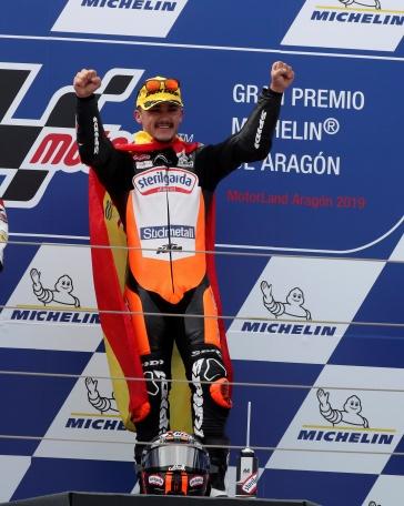 El español Arón Canet (c) celebra en el podio su victoria en el Gran Premio de Aragón de Moto3 que se ha disputado en el circuito Motorland de Alcañiz, por delante del japonés Ai Ogura (i) y el italiano Dennis Foggia (d). EFE/Javier Cebollada