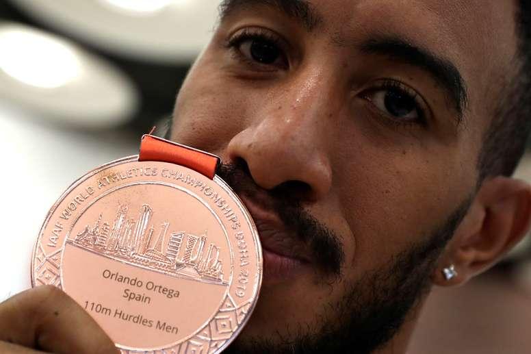 El atleta Orlando Ortega muestra su medalla de bronce a la llegada de la selección española de atletismo de los Mundiales de Doha, este lunes en el Aeropuerto de Madrid-Barajas. EFE/J.J. Guillén