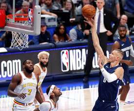 Dallas Mavericks player Kristaps Porzingis of Lativa (R) takes a shot against the Golden State Warriors in the first half of their NBA basketball game at the American Airlines Center in Dallas. EFE/EPA/LARRY W. SMITH