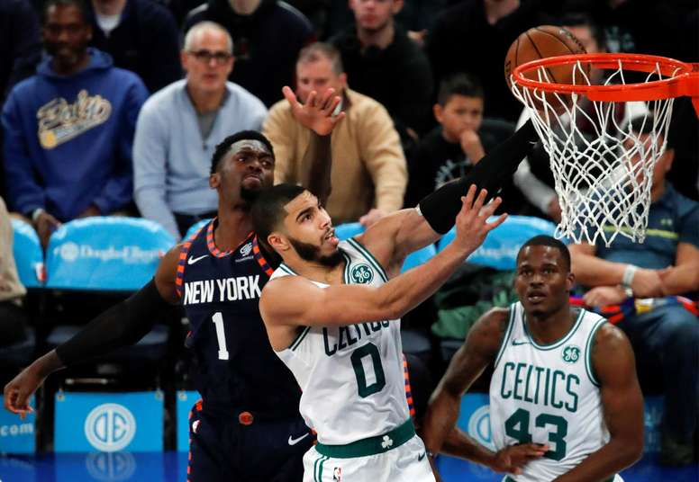 Boston Celtics forward Jayson Tatum (C) tries to put up a shot past a defending New York Knicks forward Bobby Portis (L) in the first half of the NBA basketball game between the Boston Celtics and the New York Knicks at Madison Square Garden in New York, USA, 01 December 2019. EFE/Jason Szenes