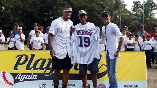 Marc Anthony (d) y el pelotero de los Chicago Cubs, Javier Báez (i), posan junto al pelotero de Little Leagues de Puerto Rico Owen Negrón (c), en la ceremonia de inauguración de un campo de béisbol recientemente renovado, hoy sábado en Loíza. Anthony y Báez celebraron este sábado la reconstrucción de un campo de béisbol en la localidad puertorriqueña de Loíza, que fue destruido por los huracanes Irma y María en 2017. EFE/Thais Llorca