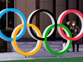 Dos mujeres, una de ellas protegida con mascarilla, conversan junto a la sede de los Juegos Olímpicos, cerca del Estadio Olímpico de Tokio, donde está prevista la ceremonia de apertura. EFE/Kimimasa Mayama