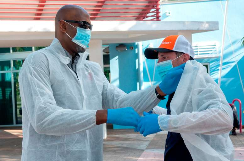 NBA Hall-of-Famer Alonzo Mourning (L) helps Scott Harris , DeliverLean CEO, wear his protective clothing before they start delivering of bags of food made by DeliverLean to homeless and low income persons in Overtown Miami, Miami, Florida, USA, 25 March 2020. EFE/CRISTOBAL HERRERA