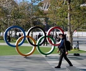 Un hombre con mascarilla pasa junto a los aros olímpicos situados frente al Estadio Olímpico de Tokio, Japón. EFE/ Antonio Hermosín