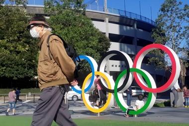 Un hombre protegido por una máscara para evitar posibles contagios da la espalda a los anillos olímpicos instalados en Tokio el 20 de marzo de 2020. EFE/Demófilo Peláez/Archivo