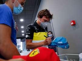 GREl piloto Fernando Alonso firma una gorra a un aficionado este miércoles en el museo que tiene en el municipio asturiano de Llanera. El español Fernando Alonso ha anunciado que en 2021 volverá a competir en el Mundial de Fórmula Uno con Renault, con la que ganó sus dos títulos mundiales -2005 y 2006-, en la que será su tercera etapa en la escudería francesa. EFE/J.L. Cereijido