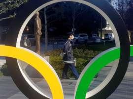 Un policía protegido por una máscara para evitar posibles contagios pasea junto a los anillos olímpicos instalados en Tokio. EFE/DEMÓFILO PELÁEZ/Archivo
