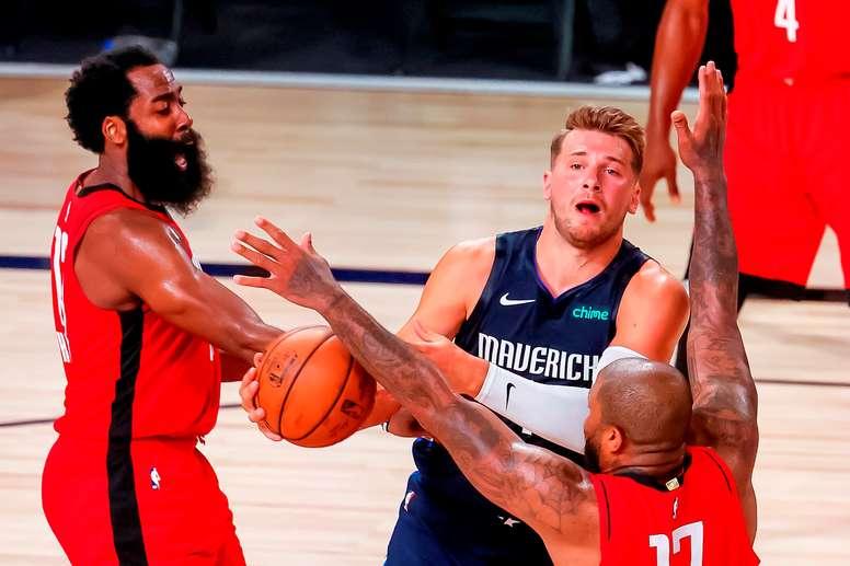 El jugador de los Dallas Mavericks Luka Doncic (c) y los de los Houston Rockets P.J. Tucker (d) y James Harden (i) durante el partido. EFE/EPA/ERIK S. LESSER
