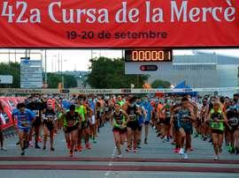 Varios corredores mantienen la distancia de seguridad al tomar la salida, que ha sido escalonada, en la primera serie de carreras de la primera jornada de la 42 edición de la Cursa de la Mercè. EFE/Toni Albir